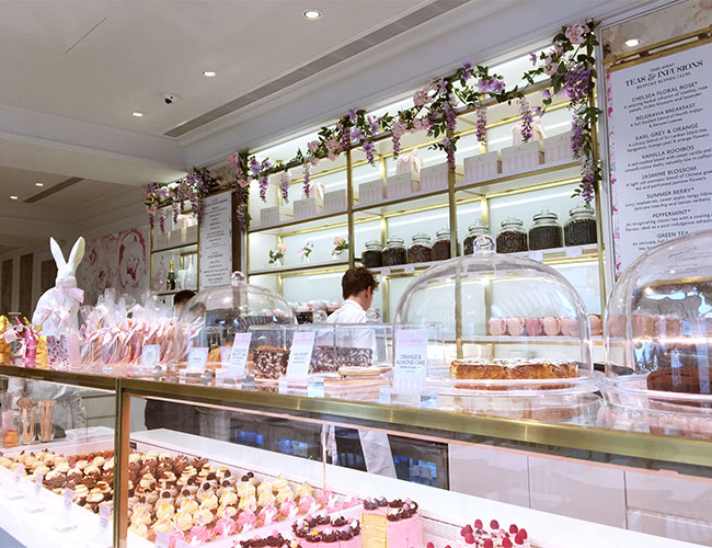 Dominating the entrance is the white marble counter featuring a longbrass framed chilled display. These materials continue through to the  rear counter with high displays of seasonal gifts and glass jars filled with coffee beans.. The  feminine brand spirit comes from pastel point of sale and merchandise, loosely draped flowers and pink patterned floor tiles.