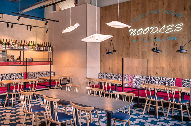 Bold patterns of hand glazed tiles and clashing geometric shapes of upholstery have been carefully chosen to compliment warm plywood throughout the restaurant.