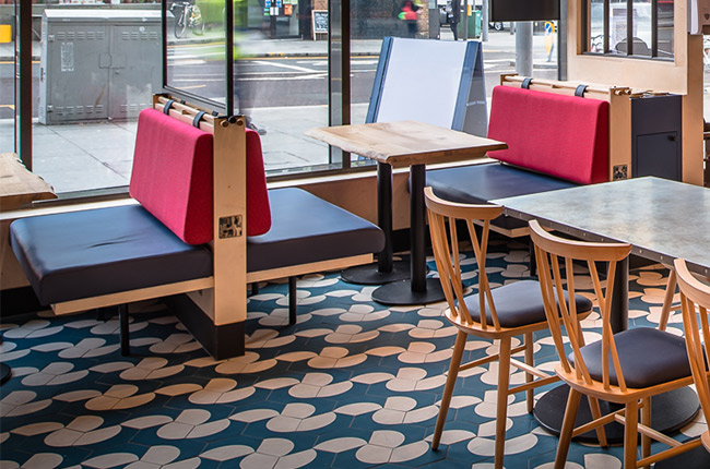 Window positioned booth seating in Walthamstow restaurant features beuilt in coathooks and data sockets for diners