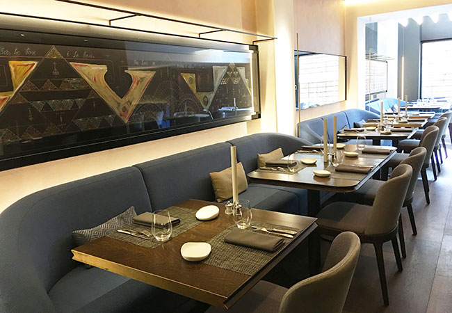 Mere restaurant features the dark wood flooring, grey and blue soft furnishings and pale walls adorned with large wall mirrors and illuminated traditional Samoan art.