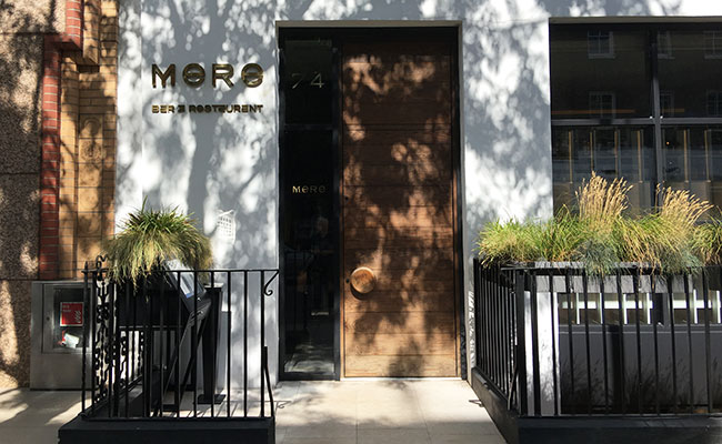 Mere restaurant designers created an elegant exterior with modern and minimalist white render walls and a tall timber door.