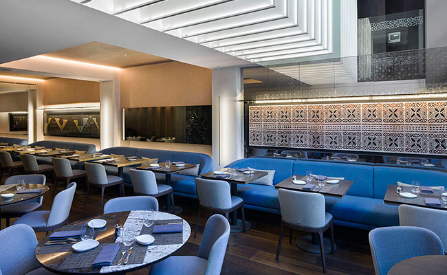 Mere restaurant architects in created a double height space with fluted white...