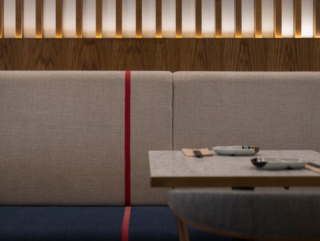 Decorative seat trimmed with a single red stripe, alluding to the Japanese practice of gift wrapping  with red rope -  MIzuhi