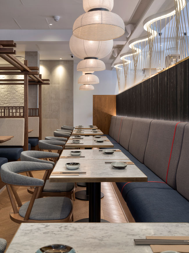 Japanese banquette seating with large paper lanterns above. Delicate wavy rope screen helps delineate the seating between two areas whilst providing light at the same time.